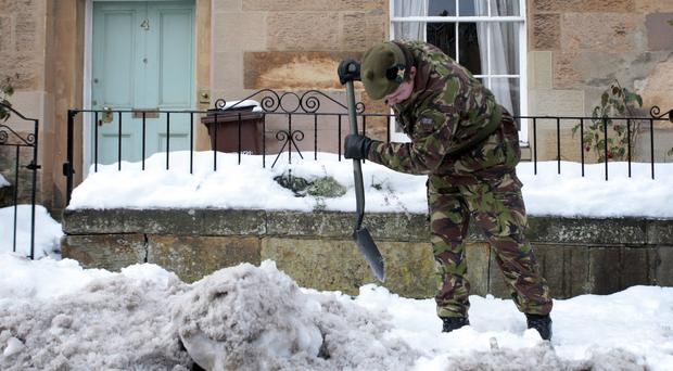 Army personnel clear snow from roads in Edinburgh in December 2010 (David Cheskin/PA Wire)