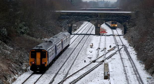 Trains pass over snow covered tracks near to Hunts Cross Station, Merseyside (Peter Byrne/PA)