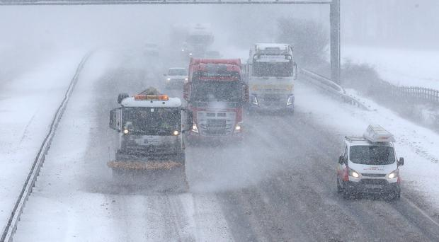 A snow plough on the M9 near Falkirk in heavy snow