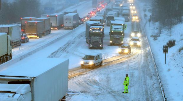 Drivers manoeuvre their cars past stationary lorries on the M80 Haggs in Glasgow (Andrew Milligan/PA)