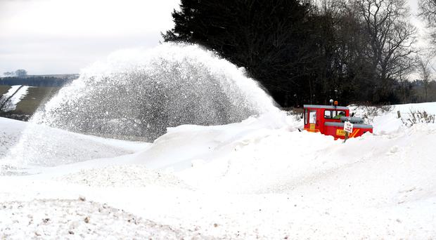 A snowblower clears the road to a small Hamlet in Cumbria (Owen Humphreys/PA)