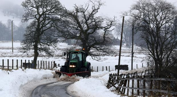 A tractor clears a rural road in the Carron Valley near Stirling, following the recent severe weather (Andrew Milligan/PA)
