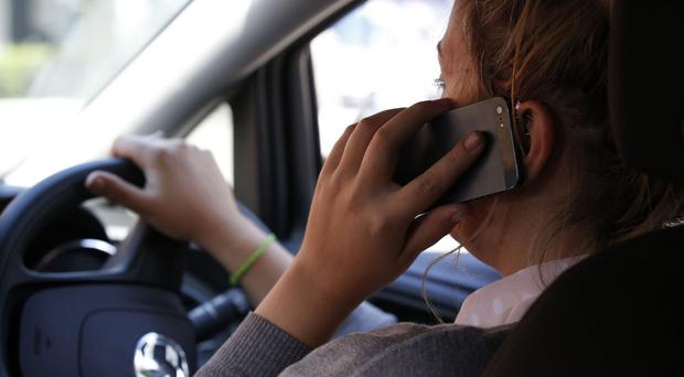Changes could also be introduced that would make it illegal to hold a phone while driving (stock image)