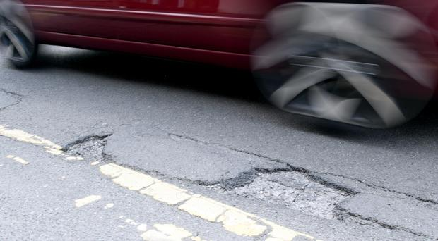 Councils have been forced to cut back on services including road repairs (Tim Goode/PA)