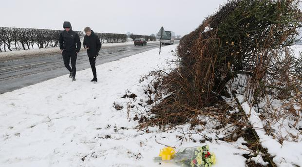 Two youths pass flowers at the scene on the A61 near Thirsk in North Yorkshire where two teenagers died and two children are among seven injured after a crash (Owen Humphreys/PA)