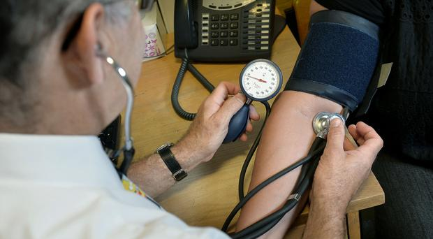 A GP checking a patient's blood pressure as new research on hypertension is considered (PA)