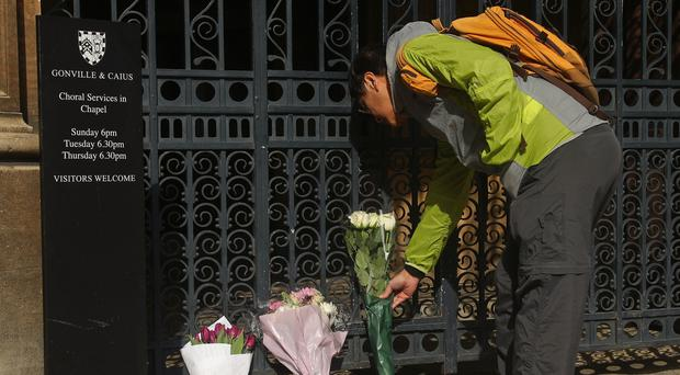 A man lays flowers outside Gonville and Caius College, Cambridge (Yui Mok/PA)