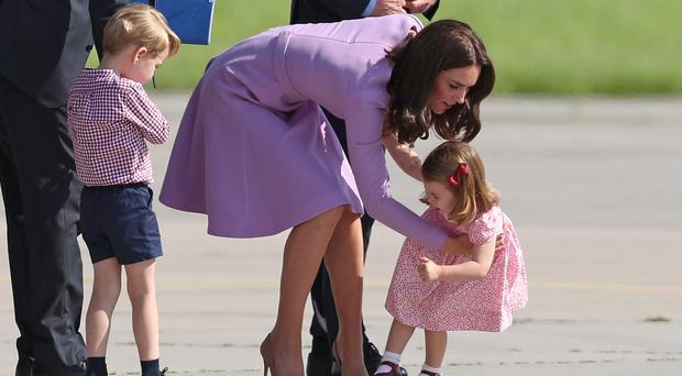 Princess Charlotte is helped up by the Duchess of Cambridge after she fell over during a visit, with Prince George and her husband the Duke of Cambridge, to Airbus in Hamburg, Germany (Jane Barlow/PA)