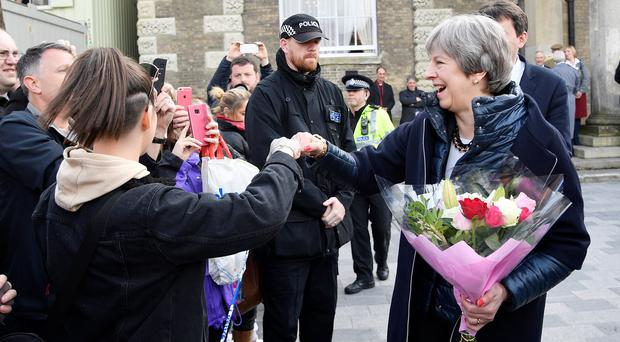Theresa May bumps fists with a member of the public in Salisbury (Toby Melville/PA)