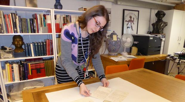 Archivist Rachael Jones cataloguing at the Glasgow School of Art with some of the letters and a photo of Francis Newbery (Glasgow School of Art/PA)