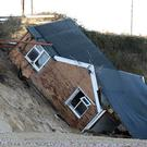 A house collapsed following a tidal surge which eroded the cliff edge on Hemsby beach in Norfolk in 2013 (Chris Radburn/PA)
