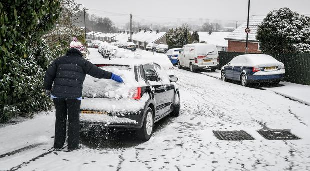 A woman cleans snow off a car in Bristol (Ben Birchall/PA)