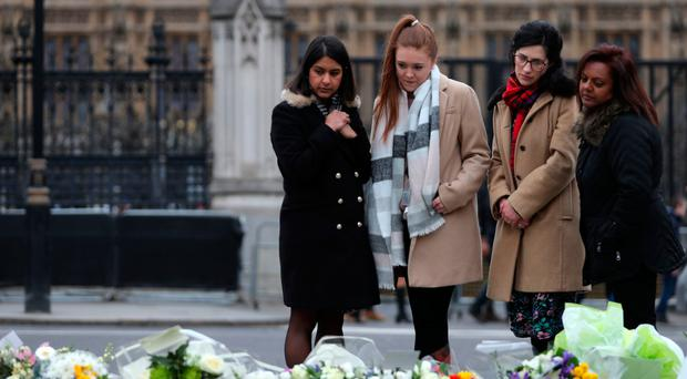 Members of the public stop to look at floral tributes left in Parliament Square in central London yesterday, a year to the day after the Westminster terror attack
