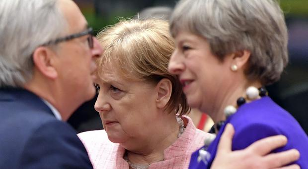 European Commission President Jean-Claude Juncker, left, speaks with British Prime Minister Theresa May, right, as German Chancellor Angela Merkel passes by during a round table meeting at an EU summit at the Europa building in Brussels (Geert Vanden Wijngaert/AP)