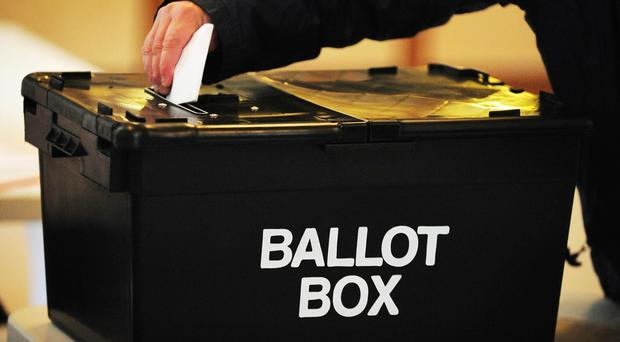 A voter places a ballot paper in a ballot box
