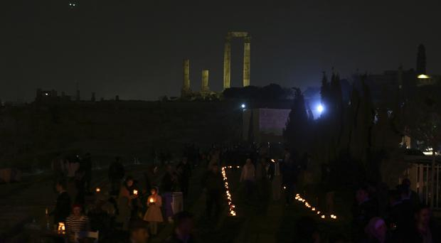 People gather at Amman Citadel to light candles that form the Earth Hour logo (Raad Adayleh/AP)