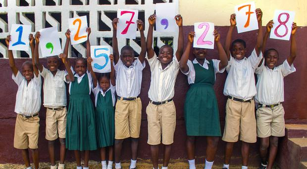 Children in Liberia help Mary's Meals mark its new milestone (Mary's Meals/PA)