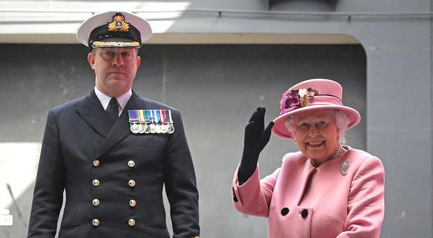 Queen Elizabeth II waves to the ships company as she leaves with the Captain of HMS Ocean, Captain Rob Pedre after the decommissioning ceremony for HMS Ocean at HMNB Devonport in Plymouth (Andrew Matthews/PA)