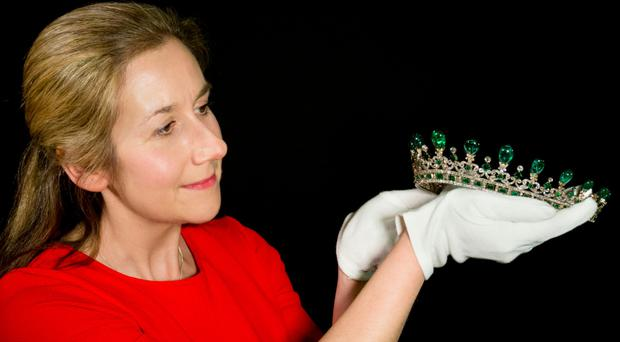 A conservator prepares the diamond and emerald diadem for display