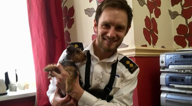 RSPCA inspector Anthony Joynes with puppy Ringo Starr, who got his head stuck in a television cabinet (RSPCA/PA)
