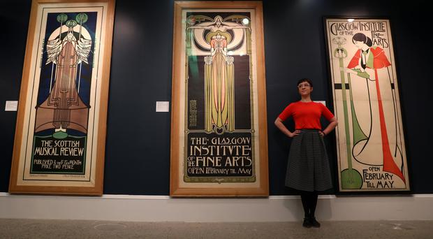 Assistant curator Hannah Willetts stands in front of posters at the launch of Charles Rennie Mackintosh Making the Glasgow Style (Andrew Milligan/PA)