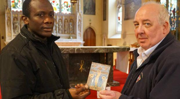 Friar Anthony Nwankwo with the damaged icon at the church in Great Yarmouth (Keith Morris/PA)