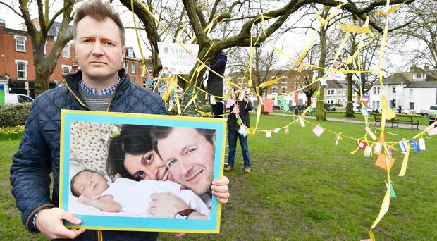 Richard Ratcliffe holds a photograph of himself with wife Nazanin and daughter Gabriella, in front of a decorated tree in Fortune Green in West Hampstead, London, on the second anniversary of Nazanin Zaghari-Ratcliffe's detention in Iran (John Stillwell/PA)