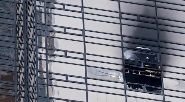 A firefighter looks out from the window of a damaged apartment in Trump Tower (Craig Ruttle/AP)VVVV