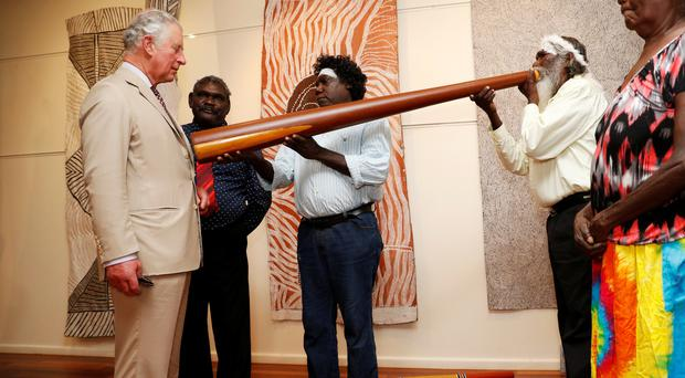 The Prince of Wales takes part in a didgeridoo demonstration during a visit to the Buku-Larrnggay Mulka Centre in Yirrkala, in Australia's Northern Territory (Phil Noble/PA)