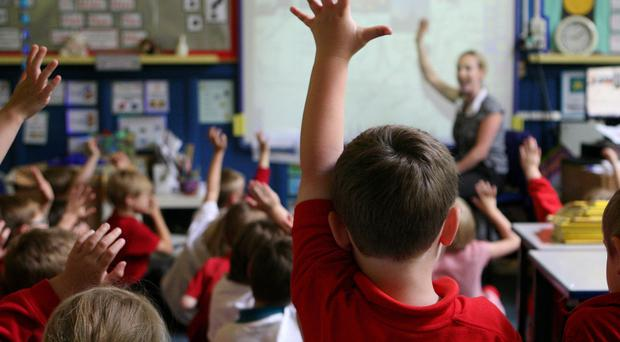 Young children at school raising their hands to answer a question as children (Dave Thompson/PA)