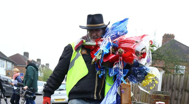 Iain Gordon takes flowers away from the scene (Gareth Fuller/PA)