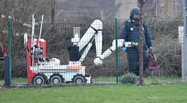 A member of the RAF bomb disposal unit and an bomb disposal robot at HM Prison Peterborough (Joe Giddens/PA)