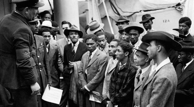 Jamaican immigrants are welcomed by RAF officials from the Colonial Office after the ex-troopship HMT Empire Windrush landed them at Tilbury (PA)