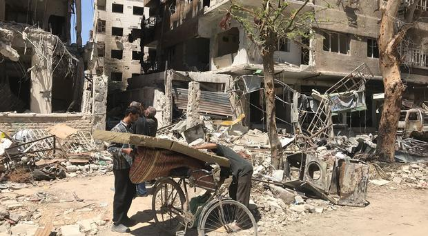 Men load a carpet and mattress on to a bicycle in front of damaged buildings in the town of Douma, the site of a suspected chemical weapons attack, near Damascus (Hassan Ammar/AP)