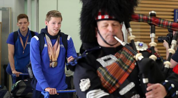 A piper greets swimmer Duncan Scott and Scottish athletes as they arrive at Glasgow Airport (Andrew Milligan/PA)