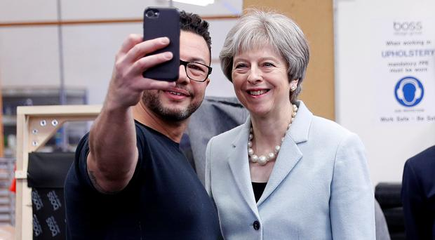 Prime Minister Theresa May poses for a selfie with upholsterer Derek Whitehouse (Darren Staples/PA)