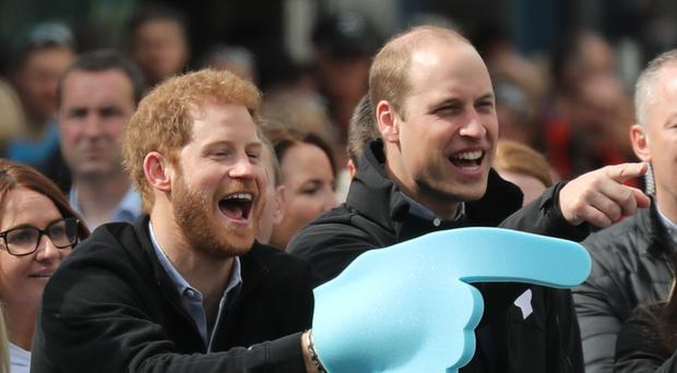 The Duke of Cambridge and Prince Harry cheering marathon runners on in 2017 (Chris Radburn/PA)
