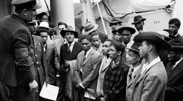 1948 photo of Jamaican immigrants being welcomed by RAF officials from the Colonial Office after the ex-troopship HMT Empire Windrush landed them at Tilbury (PA)