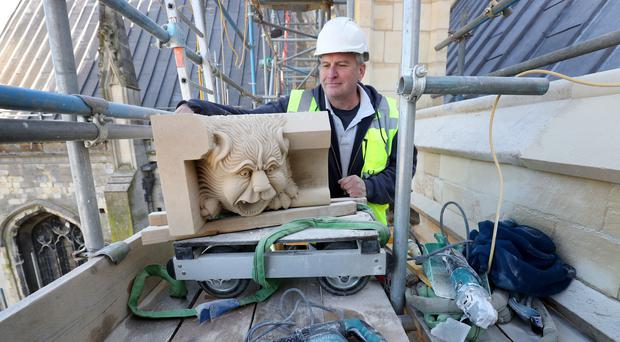 Ian Gartside, a stonemason at Canterbury Cathedral, with a gargoyle he designed and carved (Gareth Fuller/PA)