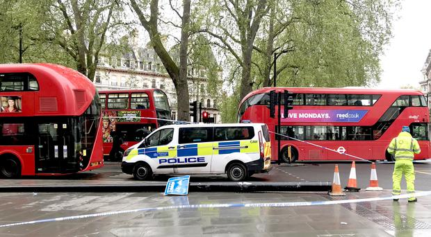 A police van attends the scene where a bus collided with a lamppost in London (Kathryn Younger/PA)