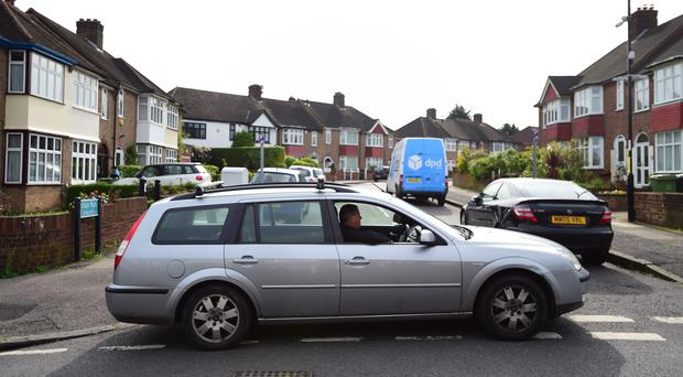 A man parks his car at the entrance to South Park Crescent in Hither Green to stop Henry Vincent's funeral cortege passing the scene of the burglar's death (David Mirzoeff/PA)