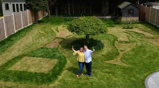 Lottery winners Sue Richards and Barry Maddox with their new lawn design, a giant champagne bottle mown into the grass