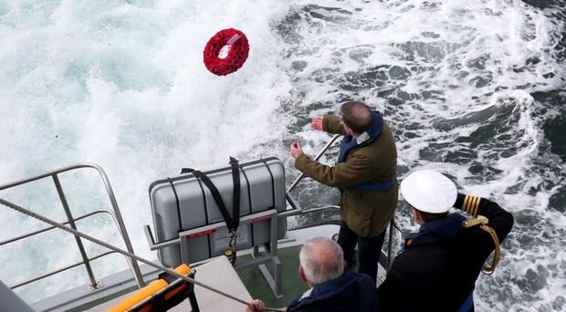 Lord George Robertson throws a wreath into the sea close to the wreck of SS Tuscania which sank in 1918 off the coast of Islay (Jane Barlow/PA)