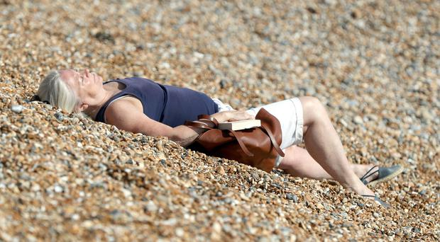 A woman enjoys the afternoon sunshine on the beach in Brighton, as Britons look set to enjoy a spring heatwave, with Bank Holiday Monday forecast to be the hottest ever (PA)