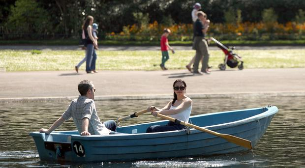 A couple enjoying the hot weather in a rowing boat in Regent's Park, London (Yui Mok/PA)