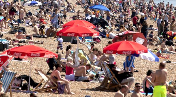 People enjoying the hot weather on Brighton beach (Steve Parsons/PA)