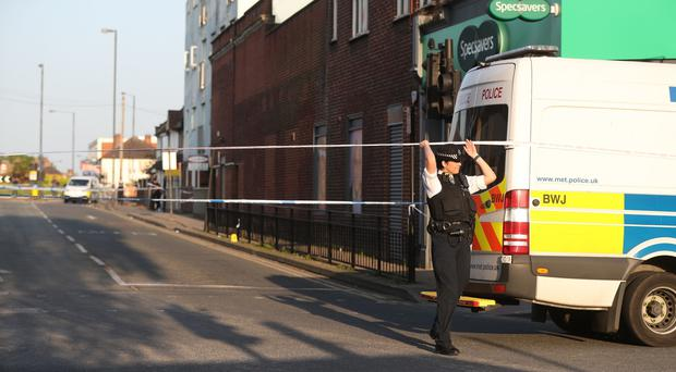 Police at the junction of Palmerston Road and the High Street, in Wealdstone (Jonathan Brady/PA)