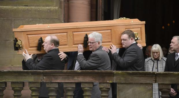 The coffin of Michael Martin, followed by his widow Mary, is carried from St Aloysius Church in Glasgow (John Linton/PA)