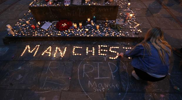 Mourners view tributes in St Ann's Square following the bombing (Jonathan Brady/PA)