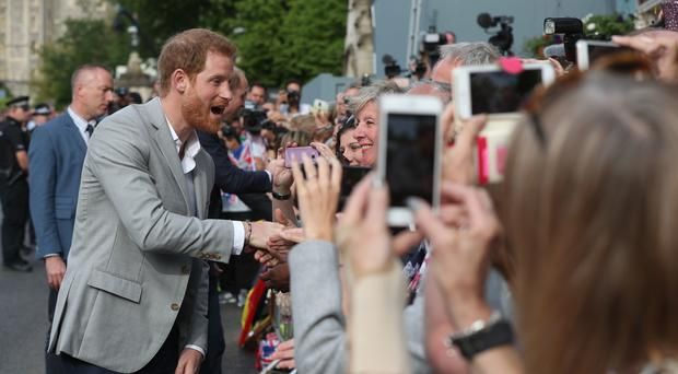 Prince Harry meets members of the public outside Windsor Castle ahead of Harry's wedding to Meghan Markle this weekend. ( Jonathan Brady/PA)